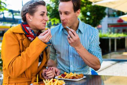Pärchen isst gemeinsam eine Currywurst mit Pommes in Berlin