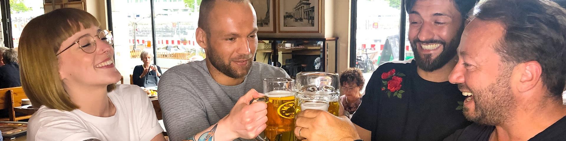 Gruppe stößt mit Bier an in der Gaststätte