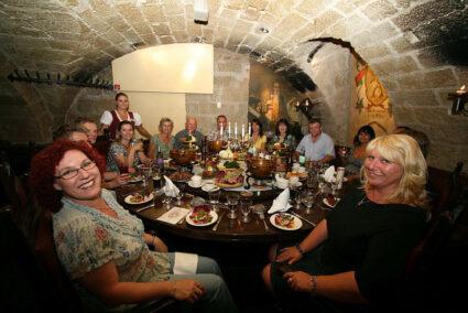 Große Gruppe isst gemeinsam im Gewölbekeller des Restaurants Sophienkeller in Dresden