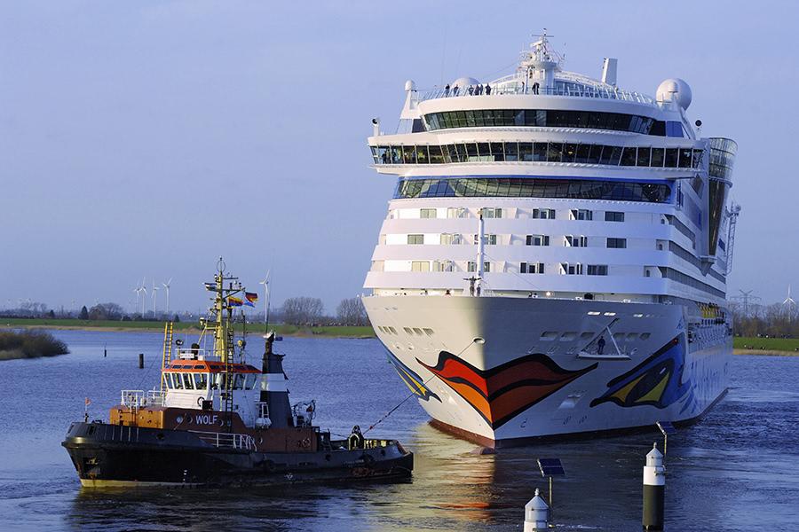 Aida-Kreuzfahrtschiff wird von eimem Schlepper in Papenburg gezogen