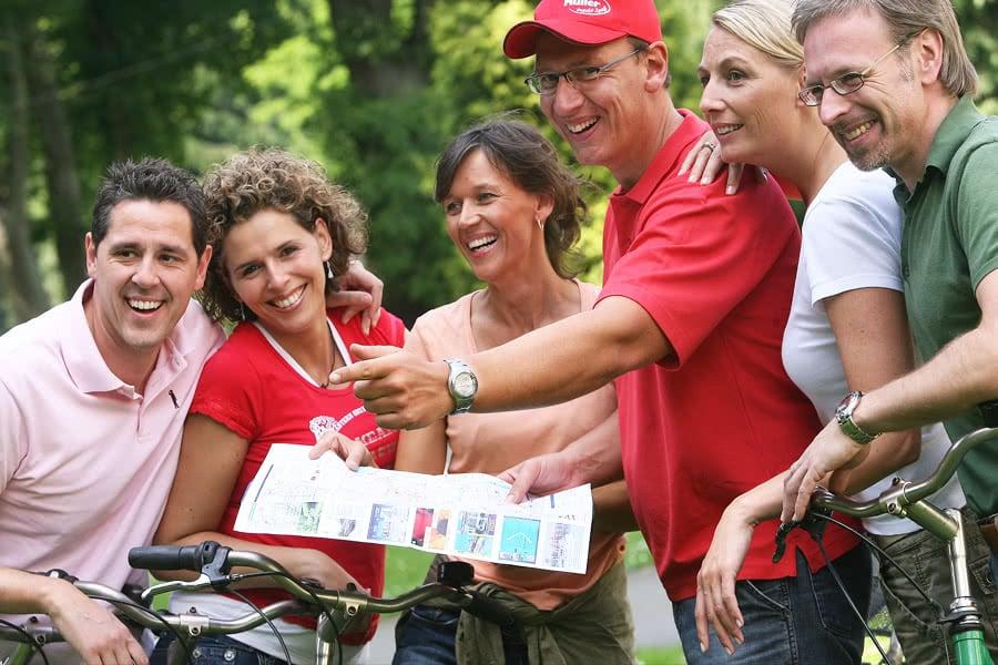 Drei Frauen und drei Männer stehen mit ihren Fahrrädern zusammen und halten eine ausgefaltete Fahrradkarte fest
